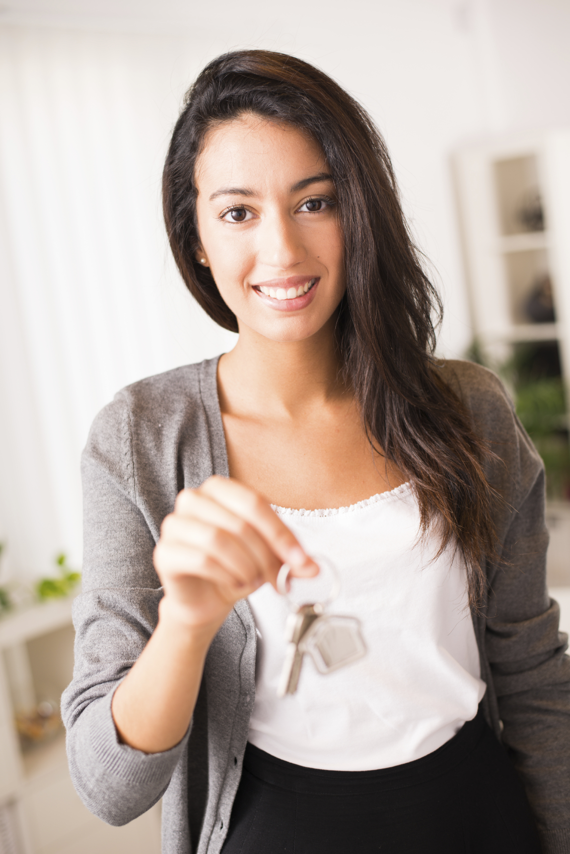 cheerful young businesswoman real estate agent holding and giving keys to a new rental house